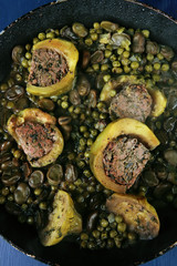 zucchini filled meat cooked with peas over blue table