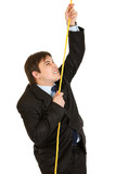 Stubborn businessman climbing up on rope isolated on white.