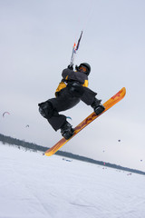 The snowkiter on the orange snowboard is jumping over the camera