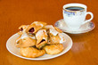 Plate of pastry and a cup of coffee on wooden table