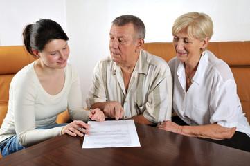 Junge Frau hilft älterem Paar beim Ausfüllen eines Formulars