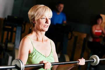 Ältere Frau macht Sport mit Langhantel im Fitnessstudio