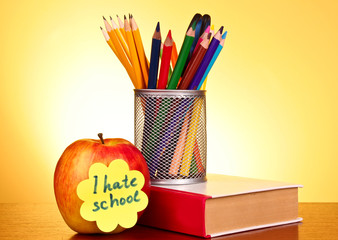 Stationery and apple on yellow background