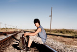 Teen boy with problems siting on rail road poster