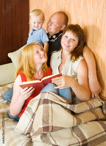 family  sitting on couch and reading