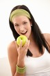 Happy young woman biting apple