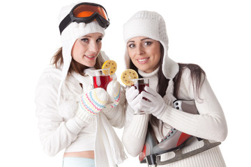 Young women with skates and skis drink mulled wine.