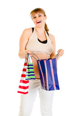 Happy pregnant woman holding shopping bags in hands