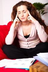 junge Frau mit Kopfschmerzen beim lernen