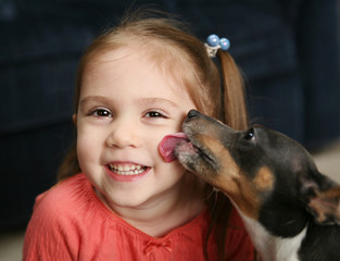 Cute girl being licked by a dog