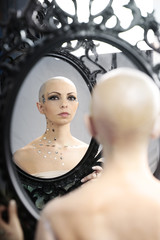Real bald cancer survivor woman looking calmly into the mirror