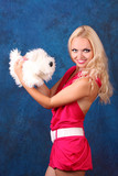 Beautiful blond girl in pink dress with small dog on blue