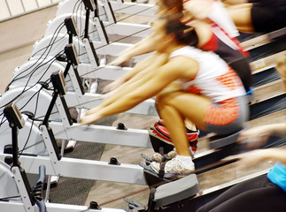 Women exercising in the gym on rowing machines