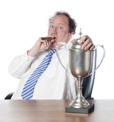 gros businessman au cigare et trophée