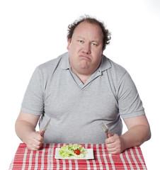 homme obèse grimaçant devant une salade verte