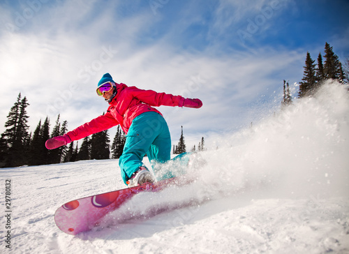 Snowboarder jumping through air with  blue sky in background