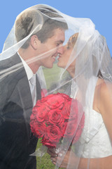 a happy bride and groom kissing under the veil