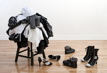 Heap of clothing on a stool and disordered shoes