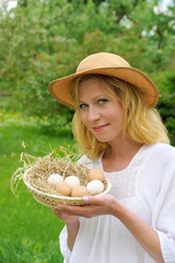Happy young woman holding fresh eggs