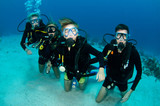family scuba diving together poster