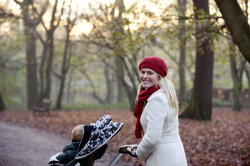 A young mother pushing a stroller in the park