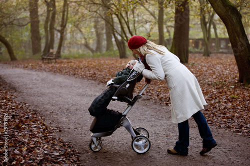 A young mother checking on her son in a stroller