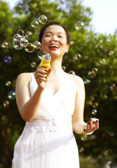 portrait of young woman blowing soap bubbles