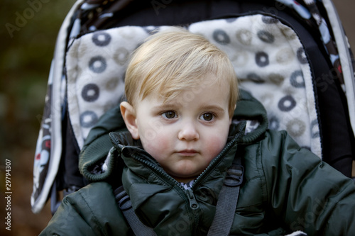 Portrait of a young boy sitting in a stroller