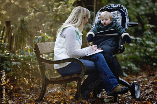 A young mother sitting on a bench, writing in a journal