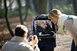 A father photographing his partner and child in the park