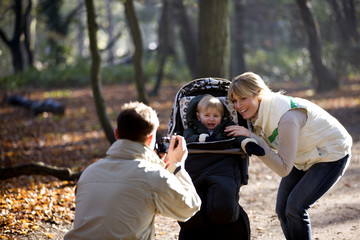 A father photographing his partner and child, child crying