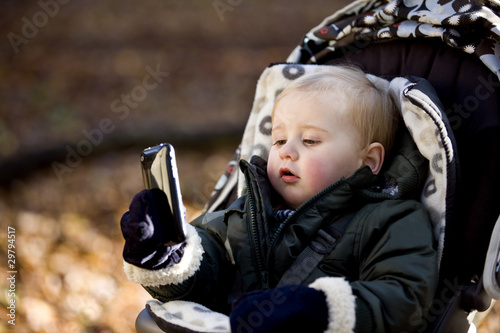 A young boy in a stroller holding an iphone