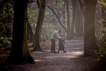 A young father checking his baby boy in a stroller, in the park
