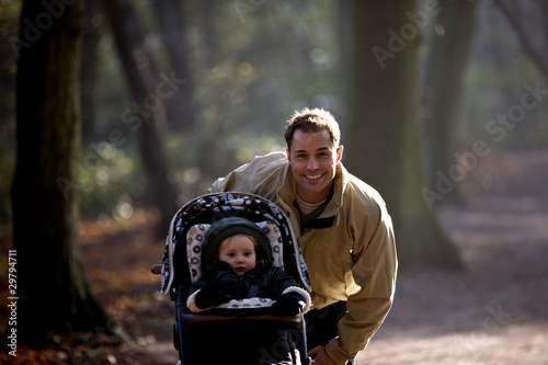 A young father standing with his son in a stroller in the park