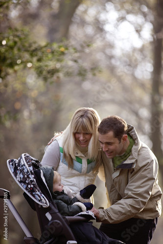 A young couple smiling at their son in a stroller