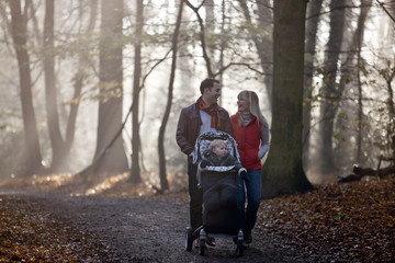 A young couple pushing a stroller in the park, laughing