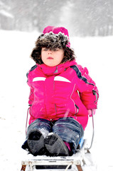 Little girl on sleigh in snowsuit