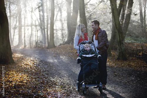 A young couple pushing a stroller in the park