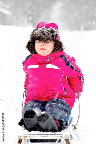 Little girl on sleigh in snowsuit