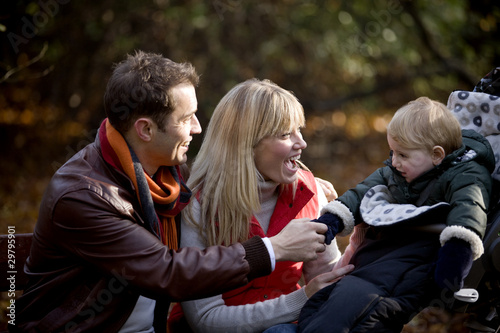 A young couple on a bench, smiling at their son in a stroller