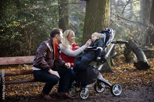 A young couple feeding their son in the park