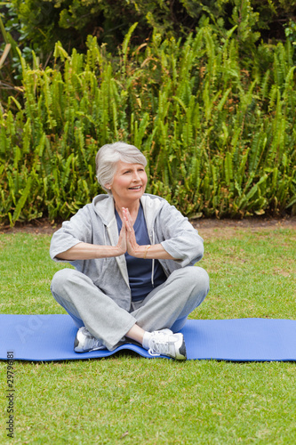 Retired woman practicing yoga in the garden