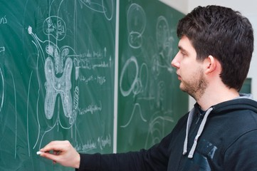Young student showing spinal chord on green chalk board