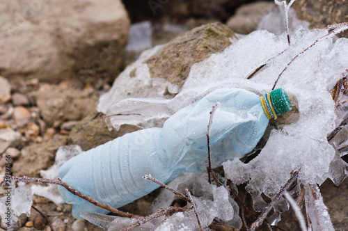 empty bottle frozen into the rocks on shore