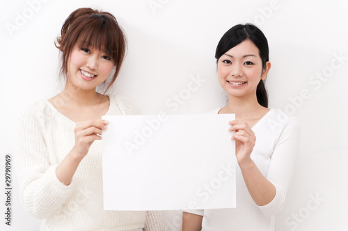 two beautiful asian women taking blank whiteboard