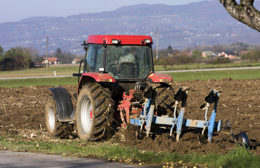 Ploughing on field with tractor.