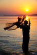 throwing fishing net during sunset