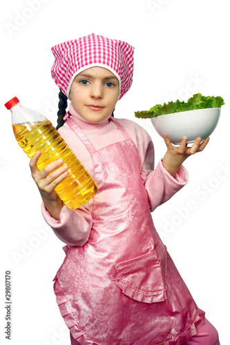 girl in an apron with the dish of lettuce and sunflower-seed oil
