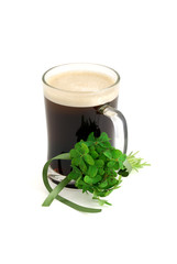 Dark beer in glass and bouquet of false shamrock with green ribb