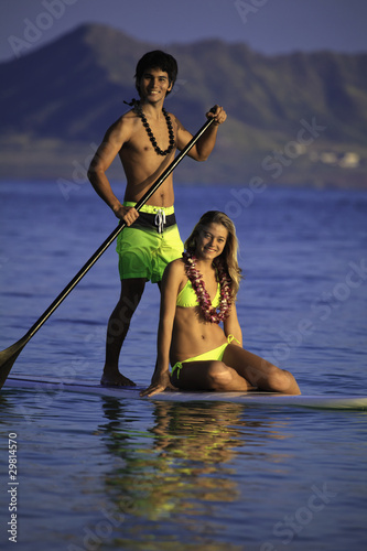 young couple on a paddleboard in a hawaii lagoon